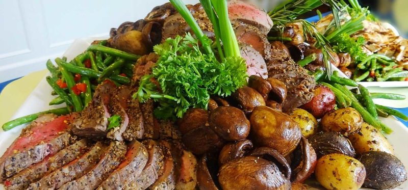 Corporate catering photo of roast beef plate with vegetables.