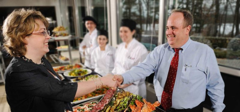 Photo of Café Services district food service manager shaking hands with client at a corporate catering event.